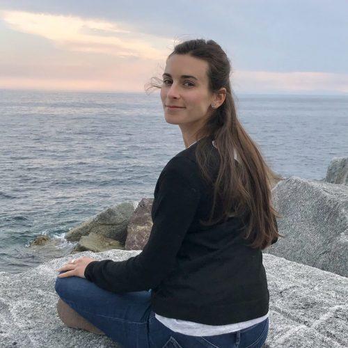 moi laura assise en méditation sur un rocher face à l'océan